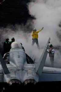 An aircraft handler directs an F/A-18C of Strike Fighter Squadron 25 (VFA-25), the Fists, into its launch position on the number one catapult during flight operations.