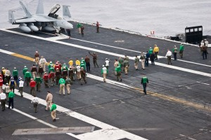 Flight deck personnel conduct a walk-down for foreign objects and debris that could damage an aircraft if ingested by the engines. Different colored jerseys distinguish various jobs on the flight deck.
