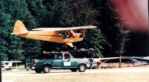 "With the exception of the DC-3, no aircraft has had as long an active life as the J-3 Cub. Here, a Piper Cub is landing on the ""world's shortest runway,"" a pickup truck at the Sussex County Airport (KWN) Air Show."