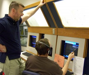 Instructor Andy Farr (left) and a student review feedback from the air traffic control voice recognition software.