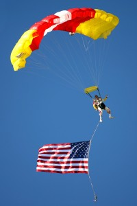 A member of the Freedom Parachute Team dives in with the American flag to start the show.
