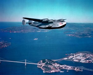 A Boeing B-314 flies over San Francisco Bay, with the San Francisco-Oakland Bay Bridge on the lower left and Yerba Buena Island and Treasure Island on the lower right. The harbor between, Port of the Trade Winds, was the home port of the flying boats.
