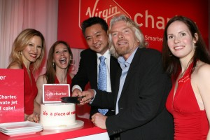 "The Virgin Angels look on as ""Entourage"" star Rex Lee helps Sir Richard Branson cut the cake in celebration of the launch of Virgin Charter."