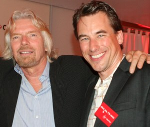 "Brian Pope, Virgin Charter's chief marketing officer, displaying a ""click me, I'm easy button,"" visits with Richard Branson."