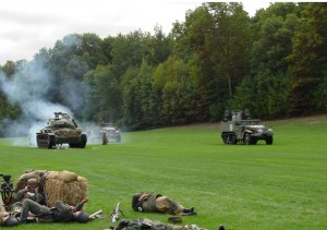 A squadron of Nazi paratroopers takes fire from an American Chaffee tank and an armored Halftrack equipped with a .50 caliber quad machine gun, during a living history re-creation at The Collings Foundation's headquarters in Massachusetts.