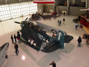 A TBM Avenger torpedo bomber awes some visitors, while others enjoy a roundtable by World War II veterans at the open house.