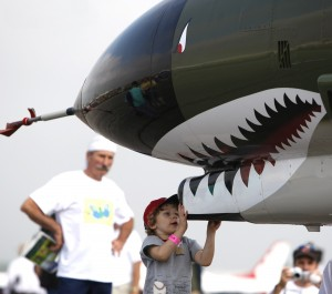 This fearless future aviator isn't afraid of the shark's teeth; he's more interested in seeing how the airplane works.