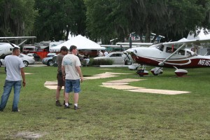 With near-bog conditions, Sun 'n Fun attendees used ingenuity and plywood planking to solve aircraft mobility problems.