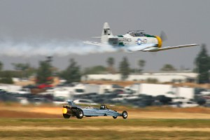 John Collver, flying his AT-6 War Dog, races Bill Braack's Air Force Reserve-sponsored jet dragster.