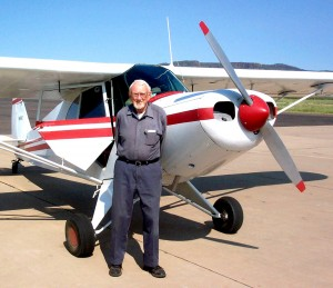 George Vose stands in front of a Piper PA-12 Super Cruiser at Alpine-Casparis Municipal Airport.