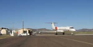 A new Gulfstream IV business jet is parked next to the small terminal building at Alpine-Casparis Municipal Airport.