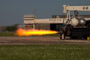 The Rocket Racing League plans to use the Armadillo Aerospace engine, seen here during a test firing. The combination of liquid oxygen and kerosene produces multi-colored exhaust flames.