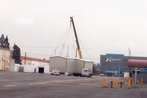 Contractors move a T-hangar to a temporary location.
