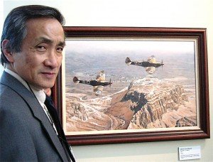 "Ronald T.K. Wong of England displays his painting, ""Merlins Over Masada,"" depicting two Israeli Air Force Spitfire Mk.IXs flying over historic Masada."