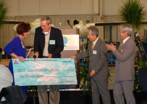 Katheryn Pennington, executive director of the Tulsa Air & Space Museum, accepted a check for $5,000 from Dennis Braner of Intercontinental Jet Service Center and Mitsubishi Heavy Industries America executives Noel Takayama and Eiichi Ishii.