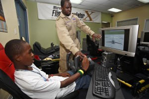 At his own Experience Aviation facility at Miami International Airport, Barrington Irving helps a student get his wings on a state-of-the-art flight simulator.