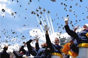 Hats fly as the U.S. Air Force Thunderbirds roar overhead at the moment of graduation.