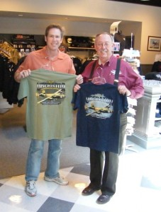 Steve Brown (left) and Lyn Fite display T-shirts for sale in the CAF American Airpower Heritage Museum gift shop.