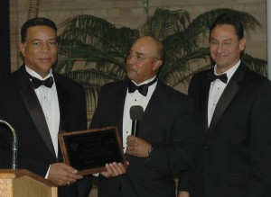Capt. Rick McCullough accepts the Shades of Blue Award from found Willie Daniels and master of ceremonies Dave Aguilera.