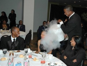 "Students from the U.S. Air Force Academy and Metro State College were recruited to help Dr. Darryl Lee Baynes with his science demonstration by pouring ""clouds"" over the guests."