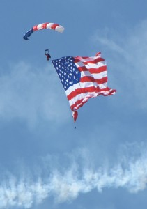 A member of the U.S. Army Golden Knights parachute team opened the daily air show by descending with a huge American flag.