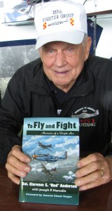 "Lt. Col. Clarence E. ""Bud"" Anderson, triple ace (16 1/4 kills) displays his book, ""To Fly and Fight""."