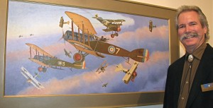 "Steve Anderson with his painting ""The Bristfits,"" a nickname for the Bristol F.2b aircraft flown by the RAF in World War I shown hacking their way through elements of German Richthofens JG1s while Sopwith Camels fight Fokker Triplanes in World War I."