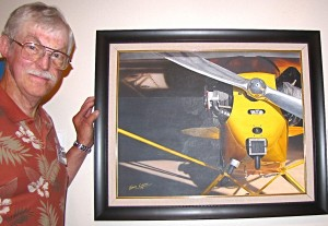 "Sam Lyons with his painting ""J-3 Morning,"" a Piper Cub he once owned. The aircraft is in the hangar awaiting routine maintenance."